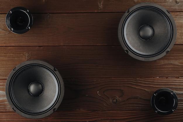 Alto-falantes de áudio automotivos pretos sobre um fundo de madeira marrom