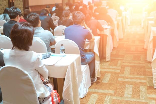 Alto-falantes no palco com vista traseira do público na sala de conferências ou reunião do seminário