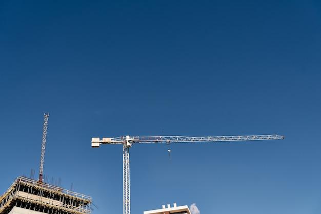 Alto guindaste de construção eleva-se sobre um canteiro de obras contra um céu azul