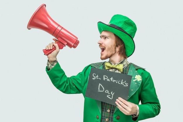 Alto jovem terno verde segurando placa escura com palavras escritas dia de são patrício.