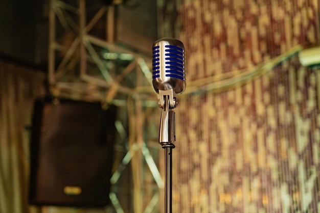 Alto microfone com inserções azuis está no centro da sala