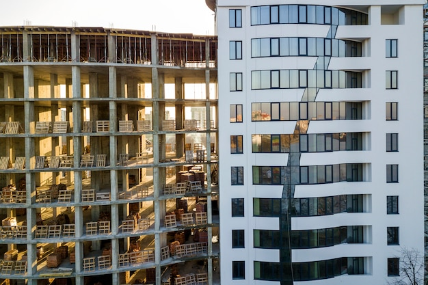 Alto multi andares apartamento ou prédio de escritórios moderno com janelas brilhantes e prédio inacabado em construção.