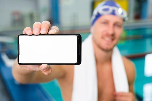 Alto, nadador masculino, segurando o telefone