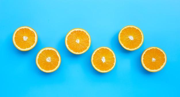 Alto teor de vitamina c, suculento e doce. fruta fresca de laranja sobre fundo azul. vista do topo