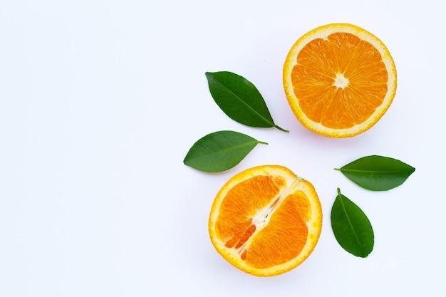Alto teor de vitamina c, suculento e doce. fruta fresca laranja com folhas verdes em branco.