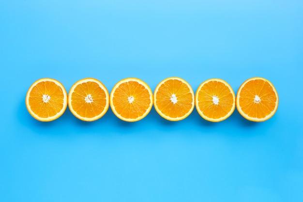 Alto teor de vitamina c, suculento e doce. fruta laranja fresca sobre fundo azul.