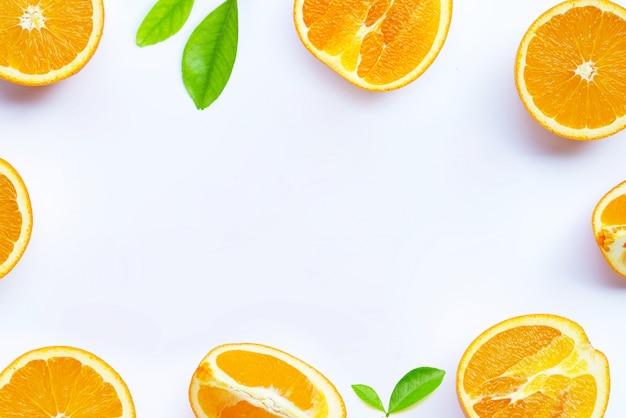 Alto teor de vitamina c, suculento e doce. quadro feito de fruta laranja fresca com folhas na superfície branca.