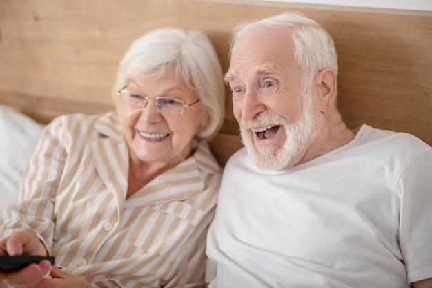 Altura de começar. mulher grisalha ligando a tv e sorrindo bem