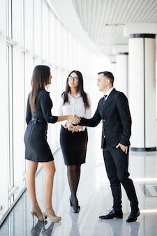 Altura total de empresário e mulher de negócios apertando as mãos em um escritório brilhante