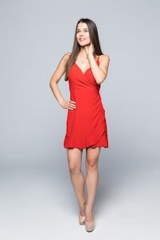 Altura total de moda atraente mulher usando um vestido vermelho fino, andando na parede.
