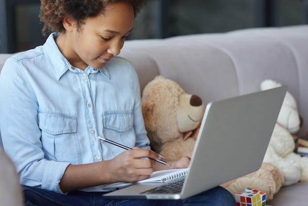Aluna adolescente alegre usando laptop fazendo anotações durante a aula online enquanto está sentada no sofá
