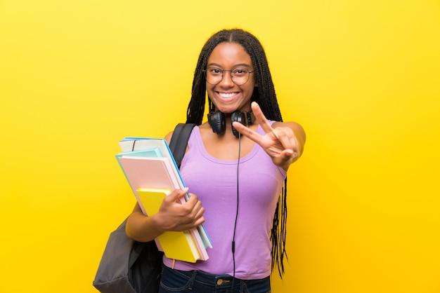 Aluna adolescente americana africano com cabelo longo trançado sobre parede amarela isolada, sorrindo e mostrando sinal de vitória