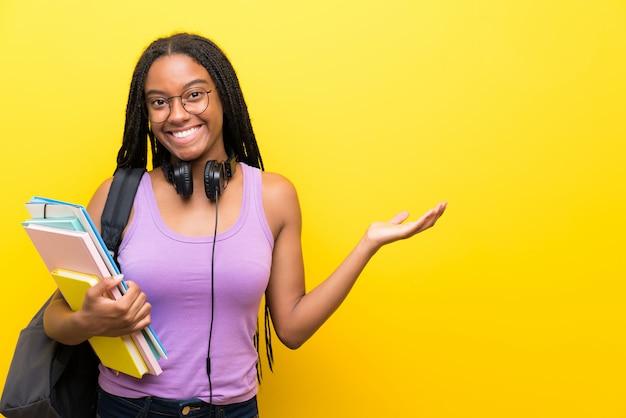 Aluna adolescente americano africano, com longos cabelos trançados sobre parede amarela segurando copyspace imaginário na palma da mão