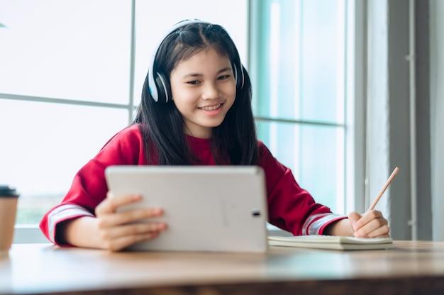 Aluna adolescente asiática usa fone de ouvido sem fio, estudo on-line com zoom reunião, jovem feliz aprender a linguagem ouvir palestra assistir webinar escrever notas olhar para laptop educação distante.
