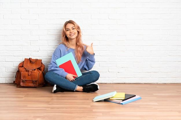 Aluna adolescente com cabelo rosa sentada no chão dentro de casa fazendo um gesto de polegar para cima