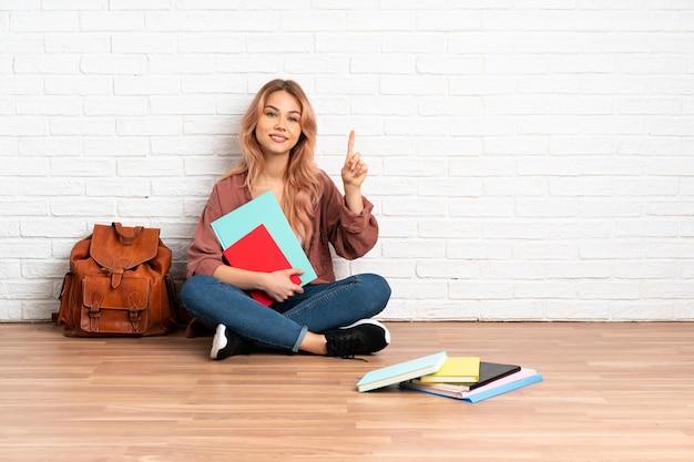 Aluna adolescente com cabelo rosa sentada no chão em um ambiente fechado, mostrando e levantando um dedo em sinal dos melhores