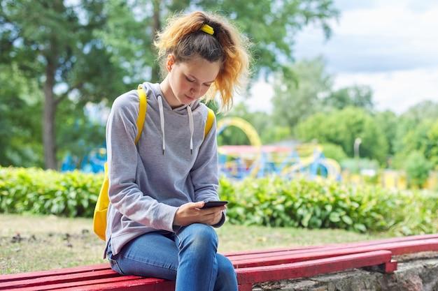 Aluna adolescente com moletom cinza sentada no banco do parque com mochila