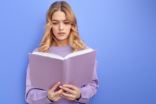 Aluna adolescente entendendo mal a trama do livro enquanto faz a lição de casa