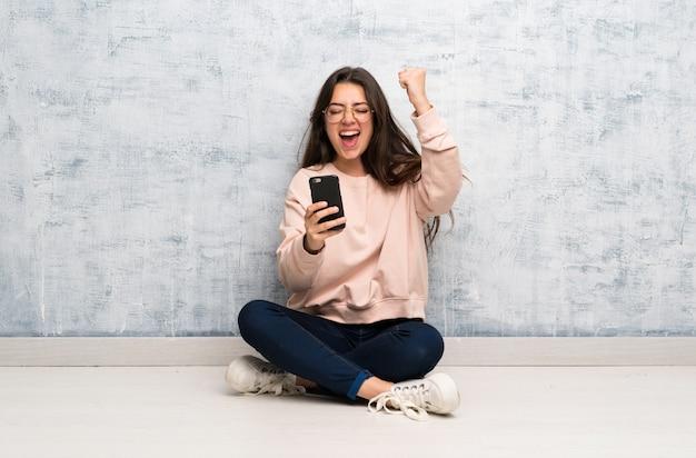 Aluna adolescente estudando em uma mesa com telefone em posição de vitória