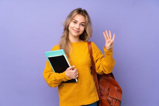Aluna adolescente isolada na parede roxa feliz e contando quatro com os dedos
