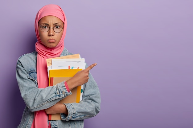 Aluna adolescente muçulmana posa com papéis e livros didáticos, aponta para o lado no espaço livre, usa óculos óticos redondos e hijab rosa