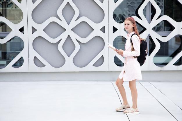 Aluna adolescente no fundo de um edifício de concreto com uma mochila nas costas