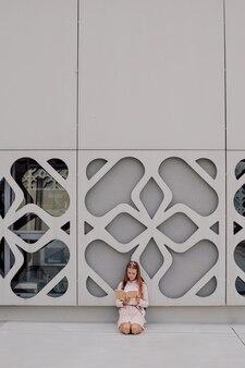 Aluna adolescente no fundo de um prédio de concreto com a mochila nas costas, copie o espaço, lendo um livro
