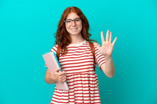 Aluna adolescente ruiva isolada em um fundo azul contando cinco com os dedos