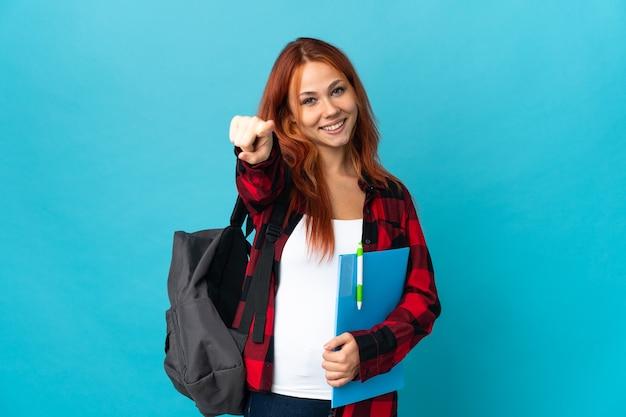 Aluna adolescente russa isolada em uma parede azul apontando para a frente com uma expressão feliz
