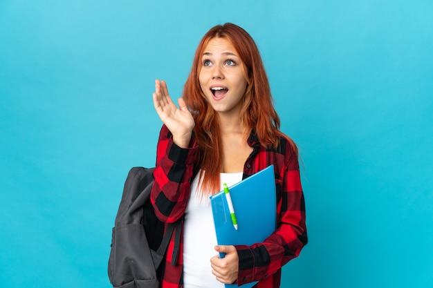 Aluna adolescente russa isolada em uma parede azul com expressão facial surpresa