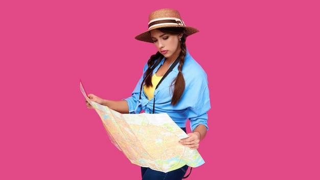 Aluna adolescente sorridente em roupas casuais e chapéu de palha, mochila e câmera digital segurando o mapa isolado no fundo rosa. mulher viajante positiva