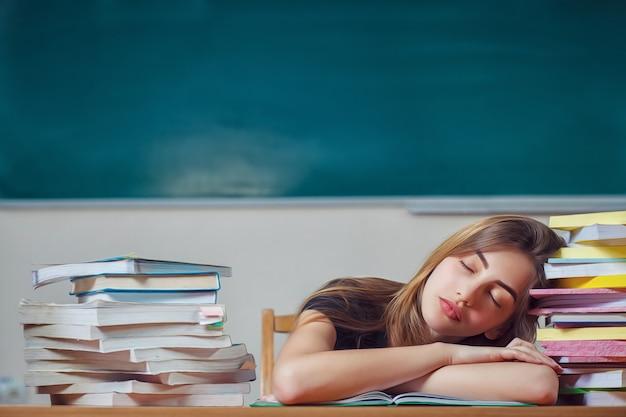 Aluna adormeceu sobre os livros. preparação para exames na escola.