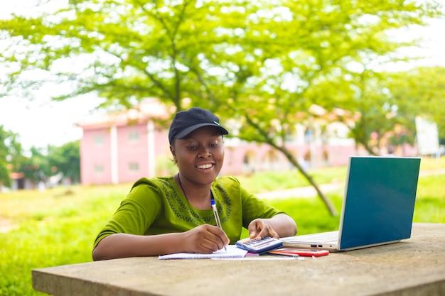 Aluna africana bonita se sentindo animada enquanto trabalhava em sua tarefa no campus