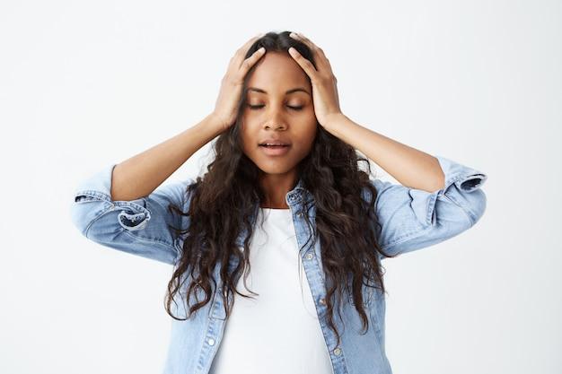 Aluna afro-americana, com longos cabelos ondulados, vestida casualmente, sentindo-se estressada, mantendo as mãos na cabeça, com os olhos fechados em frustração e desespero depois de cometer um erro grave.