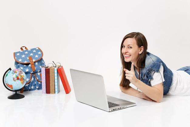 Aluna alegre apontando o dedo indicador para a frente, trabalhando em um laptop perto da mochila globo, livros escolares isolados