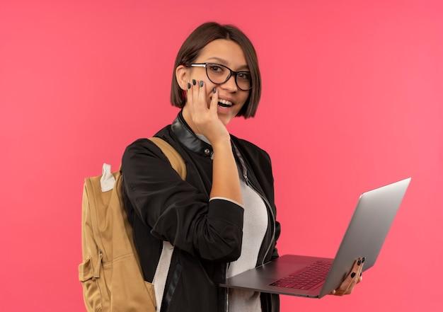 Aluna alegre de óculos e bolsa traseira segurando laptop e colocando a mão na bochecha isolada em rosa