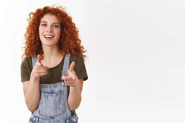 Aluna alegre e amigável ruiva de cabelos cacheados apontando pistolas de dedo para a câmera, sorrindo alegremente, parabenizando a amiga com um gesto atrevido, parada na parede branca brincalhona