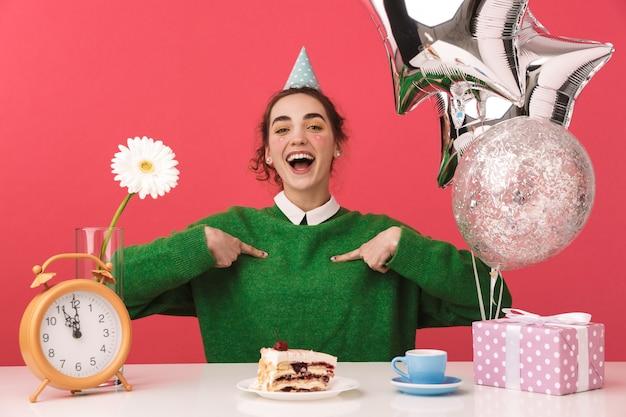 Aluna alegre e jovem nerd comemorando seu aniversário e apontando para si mesma enquanto está sentada à mesa e olhando