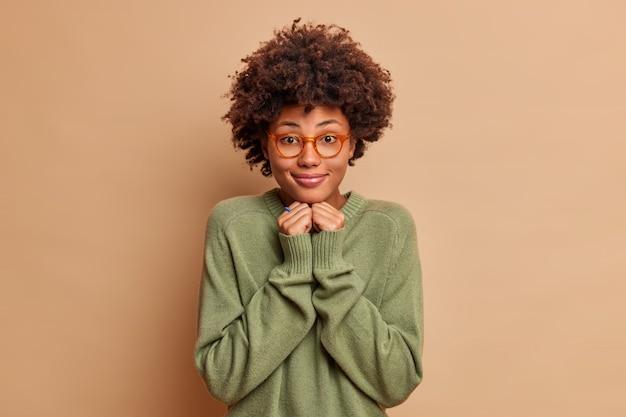 Aluna alegre e satisfeita com cabelo afro mantém as mãos embaixo do queixo, vestida com um macacão casual e usa óculos, com um sorriso encantador no rosto isolado sobre uma parede bege
