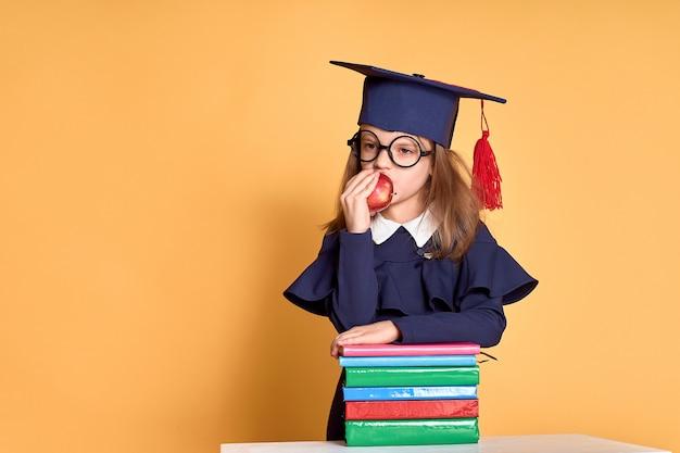 Aluna alegre em roupa de formatura carregando maçã em pé ao lado da pilha de livros didáticos