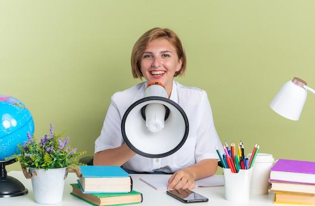 Aluna alegre jovem loira sentada na mesa com as ferramentas da escola, olhando para a câmera, segurando o alto-falante perto da boca, isolada na parede verde oliva
