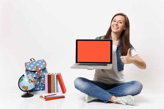 Aluna alegre segura o computador laptop pc com a tela preta em branco vazia mostrando o polegar perto do globo, mochila com livros escolares