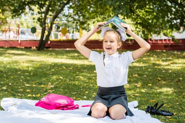 Aluna alegre segura um livro com lição de casa acima da cabeça enquanto está sentado em um cobertor em um parque ensolarado de outono. educação ao ar livre para crianças. conceito de volta às aulas