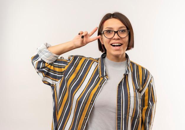 Aluna alegre usando óculos, fazendo o sinal da paz, isolado no branco Foto gratuita