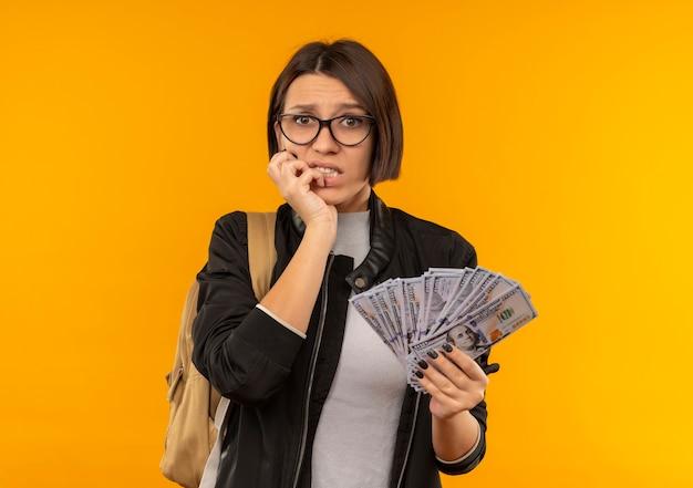 Aluna ansiosa de óculos e mochila segurando dinheiro, colocando a mão no queixo isolado em laranja com espaço de cópia