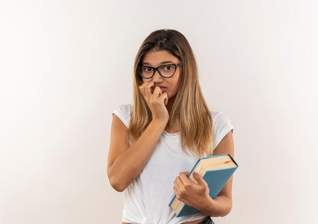 Aluna ansiosa, jovem e bonita usando óculos e mochila segurando um livro, colocando a mão no queixo