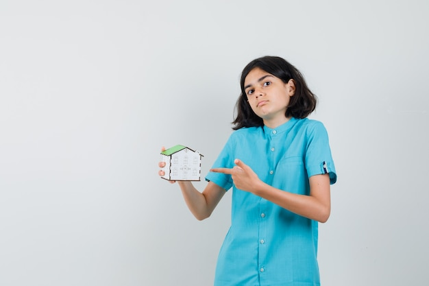 Aluna apontando para um modelo de casa de camisa azul e parecendo segura