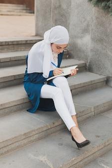 Aluna árabe sentada na escada no centro da cidade