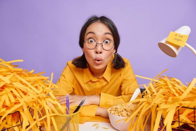 Aluna asiática atônita fica olhando chocada para os trabalhos de frente durante toda a noite em um projeto de trabalho cercado por papel cortado usa óculos redondos, camisa amarela senta na mesa isolada sobre a parede roxa