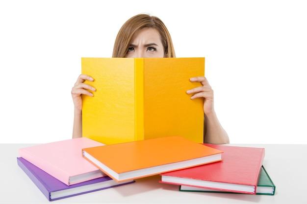 Aluna asiática estressada atrás de uma pilha de livros